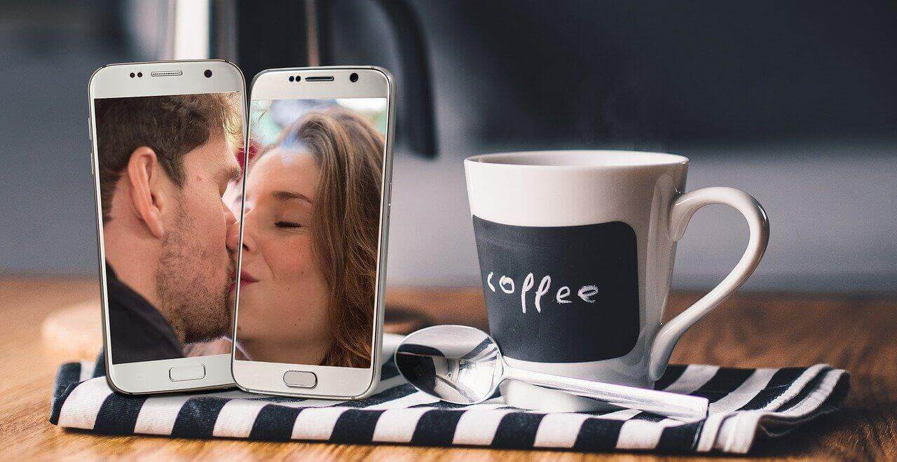 Two cell phones arranged next to each other so it looks like the people on the phone are kissing each other