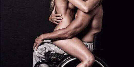 The torsos of a naked woman on the lap of a man in a wheelchair
