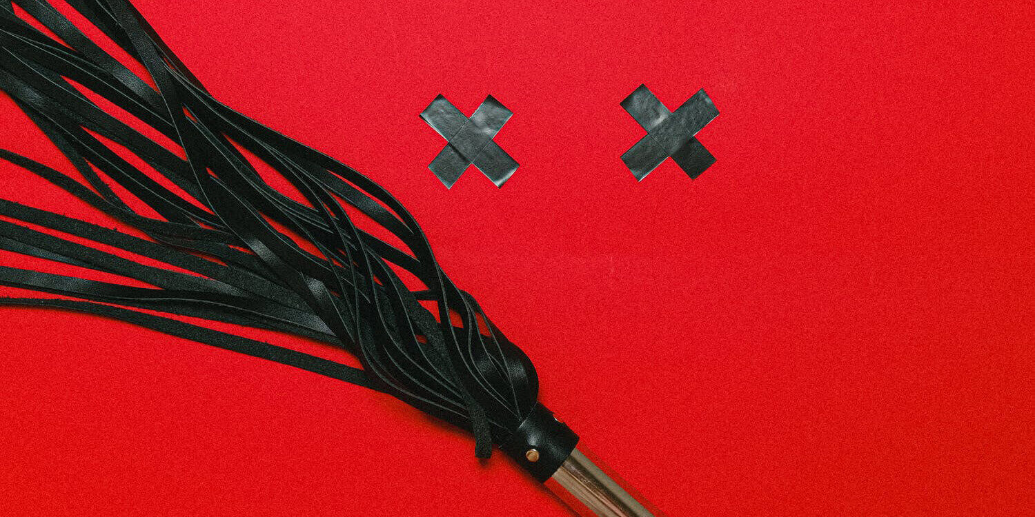 Black flogger and X pasties on a bright red background