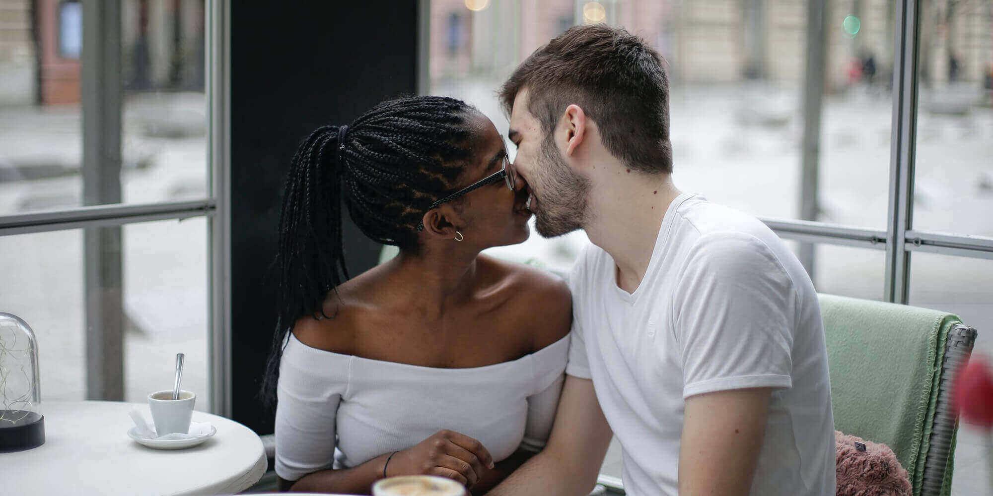 A Black woman and white man kissing