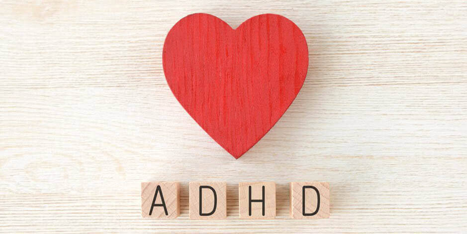 Wood background with a heart and scrabble letters that spell out ADHD